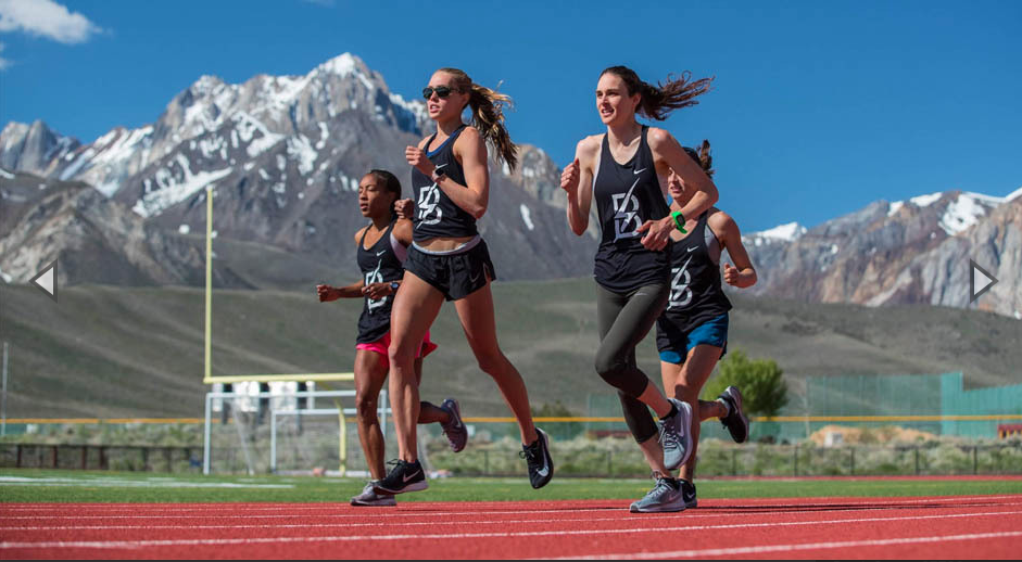 atheletes running in track near the mountain
