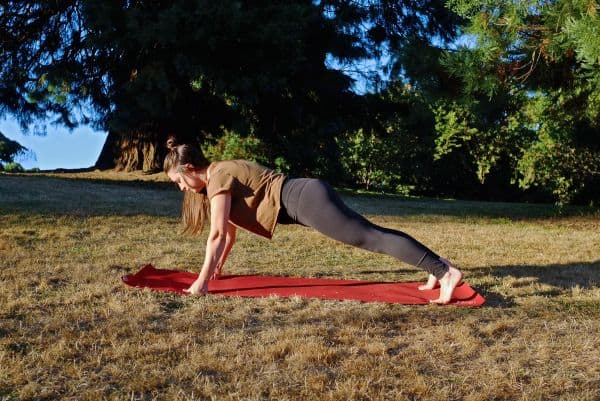 Plank variation pose of girl on red yoga mat