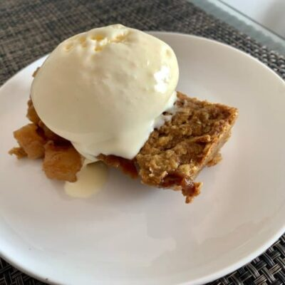 apple crisp with vanilla ice cream on top place in a white plate