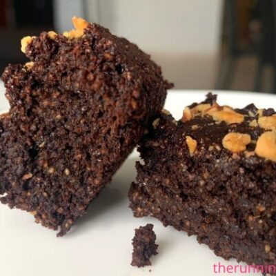 chocolate brownies on white plate with almonds toppings